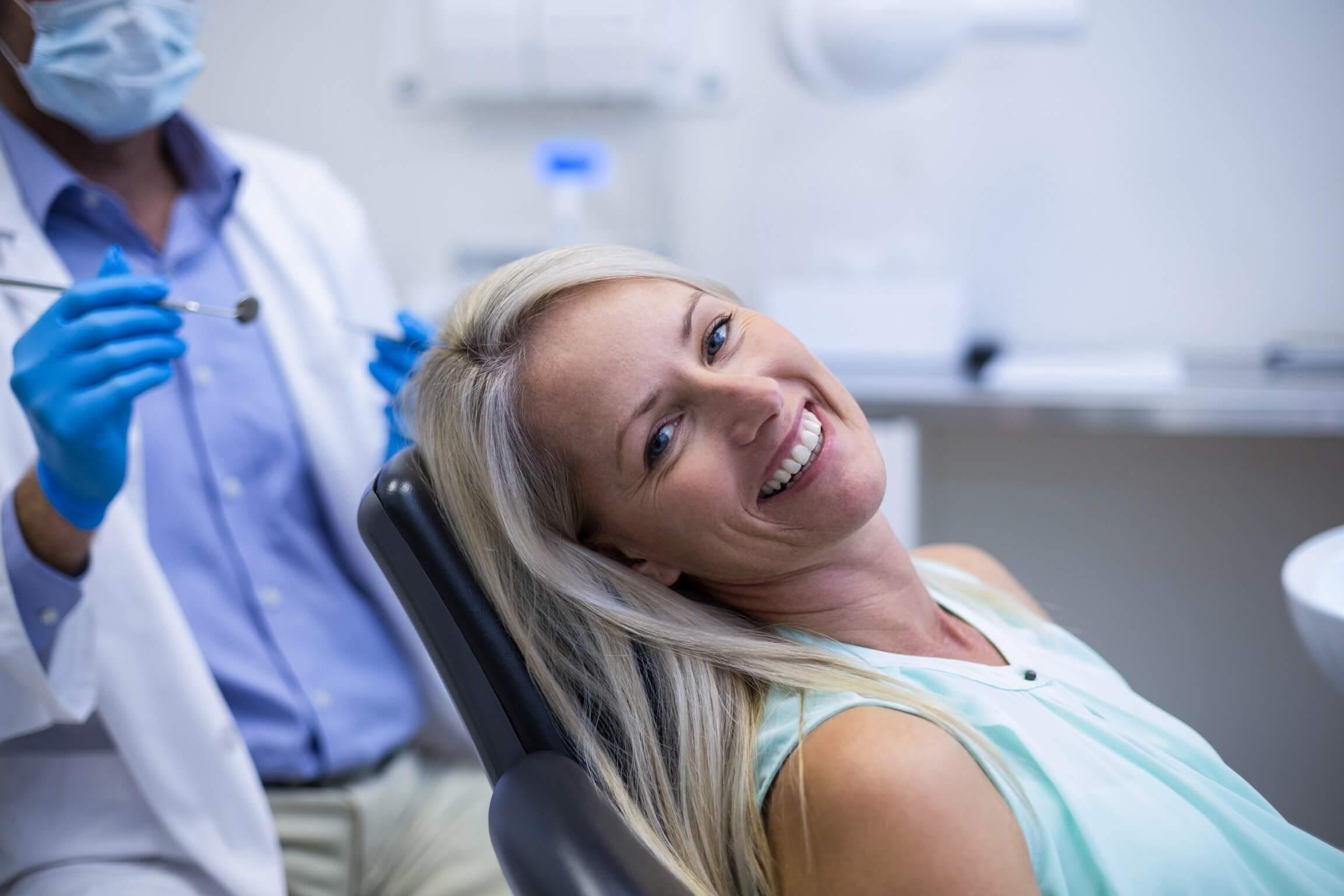 אישה מחייכת אצל רופא שיניים